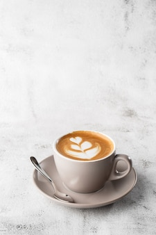 Tasse blanche de café latte chaud avec une belle texture d'art latte en mousse de lait isolée sur fond de marbre brillant. vue aérienne, espace copie. publicité pour le menu du café. menu du café. photo verticale.