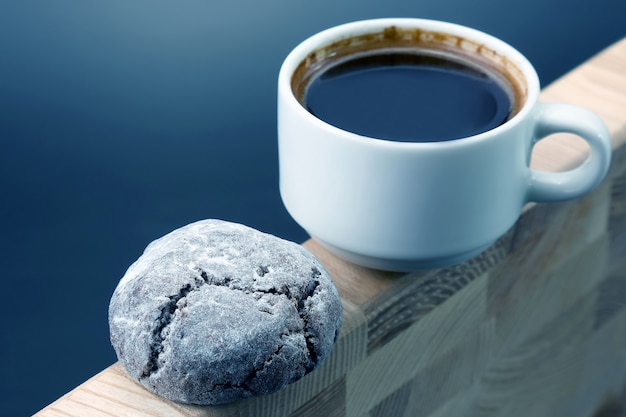 Tasse blanche de café noir avec des biscuits sur un cadre en bois. desserts