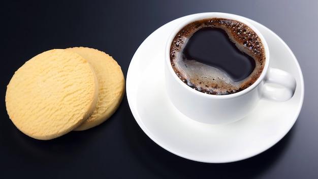 Tasse blanche de café noir avec des biscuits sur fond sombre