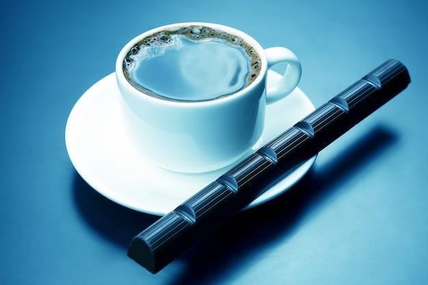 Tasse blanche avec café noir et chocolat sur la soucoupe. boisson chaude