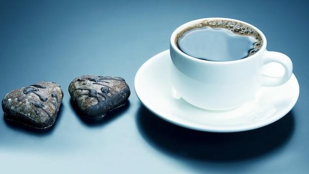 Tasse blanche de café noir avec coeur de biscuits. desserts