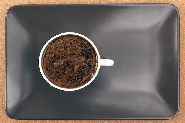 Tasse blanche de café noir sur une plaque brune. boisson chaude