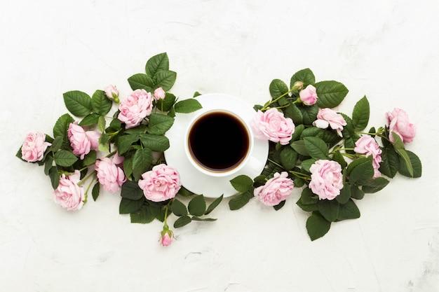 Tasse blanche avec café noir et roses roses sur une surface en pierre claire. mise à plat, vue de dessus