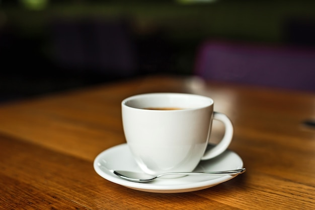 Une tasse blanche de café noir, soucoupe blanche, cuillère, table en bois, dans un café