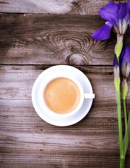 Tasse blanche avec café noir sur une surface en bois grise
