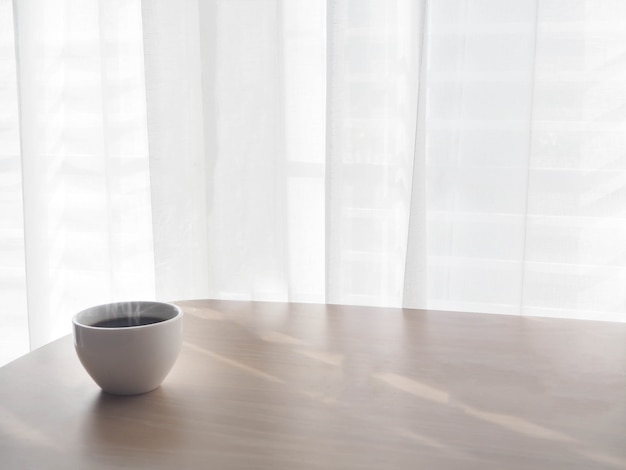 Tasse blanche de café sur la table en bois.