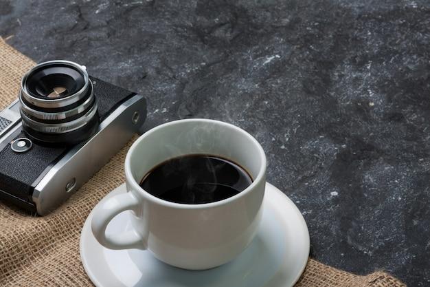 Tasse blanche café et vieille caméra sur toile de jute en pierre noire