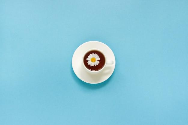 Tasse blanche de camomille de thé sur fond bleu