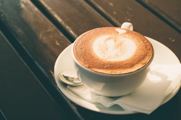 Tasse blanche de cappuccino à la cannelle sur une table en bois dans un café
