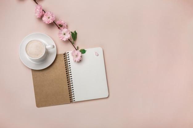 Tasse blanche avec cappuccino, fleurs de sakura, bloc-notes sur fond rose pastel