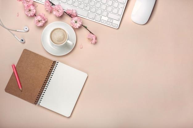 Tasse blanche avec cappuccino, fleurs de sakura, clavier, réveil, ordinateur portable
