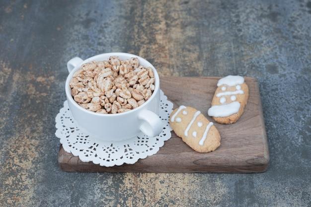 Tasse blanche avec deux pain d'épice sur planche de bois.