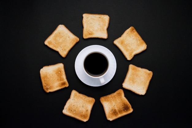 Tasse blanche avec du café et du pain grillé empilés sur un fond sombre.