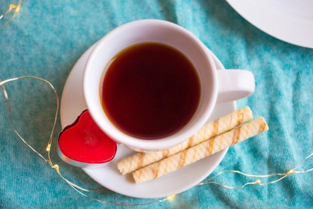 Tasse blanche avec du café ou du thé et un coeur rouge