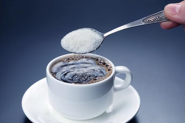 Tasse blanche avec du café noir et cuillère avec du sucre. boisson chaude