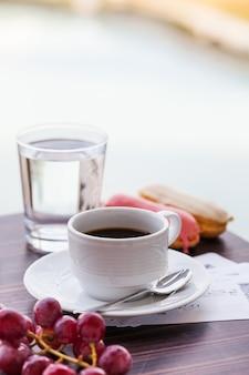 Tasse blanche avec du café noir avec des éclairs et un verre d'eau potable