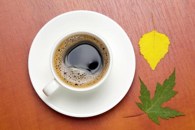 Tasse blanche avec du café noir et des feuilles d'automne. boissons chaudes