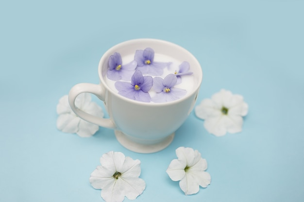 Tasse blanche avec du lait végétalien et des fleurs sur fond bleu. le concept de boissons et d'aliments végétariens, de tisanes, de beauté et de santé. salon de spa, espace copie. photo en gros plan. rincer le système