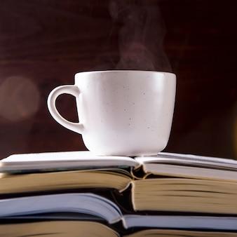 Une tasse blanche avec du thé est sur la pile de livres ouverte