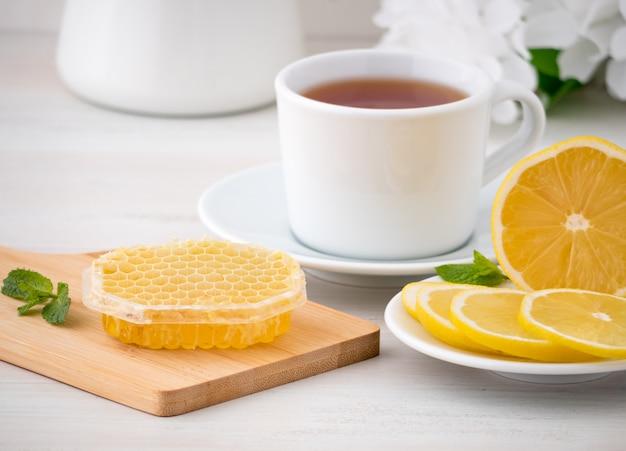 Tasse blanche avec du thé, des tranches de citron et du miel en nid d'abeille sur blanc