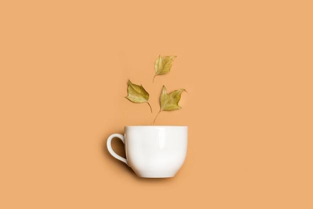 Tasse blanche et feuilles sèches sur fond marron en vue de dessus