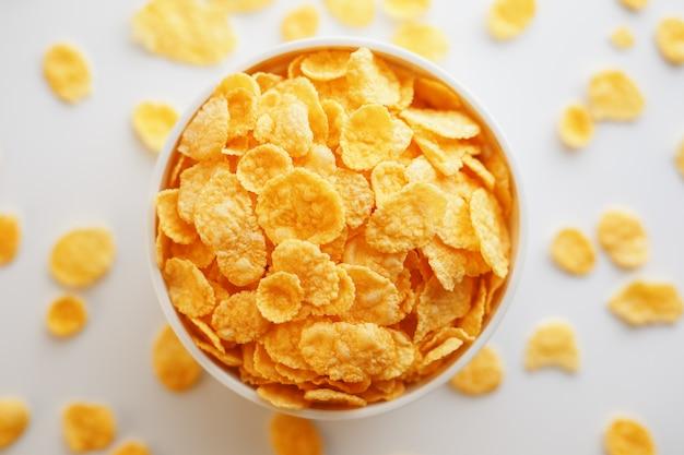 Tasse blanche avec des flocons de maïs dorés isolés on white