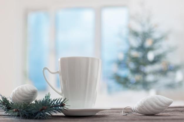 Tasse blanche sur fond sapin de noël et fenêtre