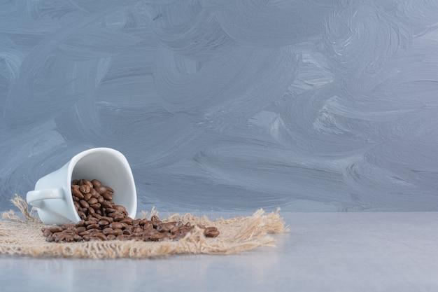 Une tasse blanche de grains de café torréfiés sur du marbre.