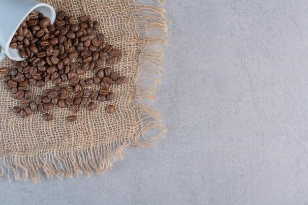 Une tasse blanche de grains de café torréfiés sur fond de marbre.