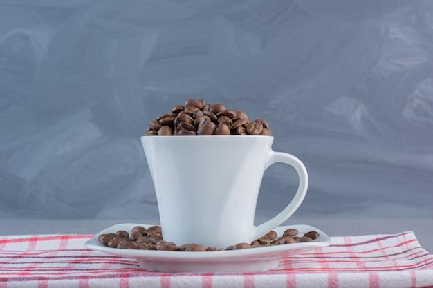 Une tasse blanche de grains de café torréfiés sur une nappe à rayures.