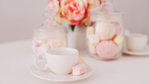 Tasse blanche avec des guimauves sur fond blanc. petit déjeuner romantique. concept de vacances, anniversaire, pâques, 14 février, 8 mars. pose à plat