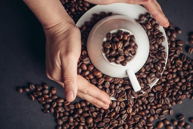 Tasse blanche inversée sur une soucoupe et des grains de café sur une vue de dessus de gros plans de table gris.