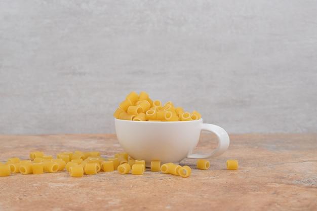 Une tasse blanche pleine de macaronis frais non préparés sur fond de marbre
