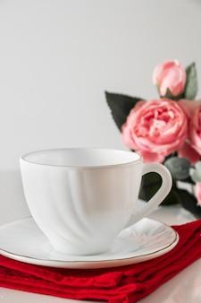 Tasse blanche pour le café sur une serviette rouge sur fond blanc
