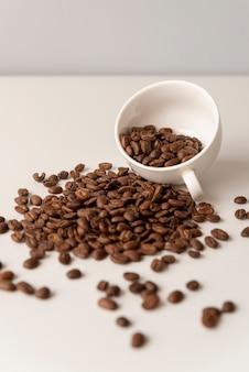 Tasse blanche remplie de grains de café