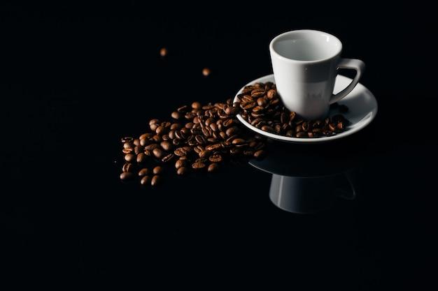 Tasse blanche renversée avec grains de café