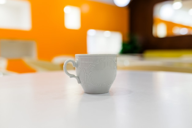 Tasse blanche sur le tableau blanc.