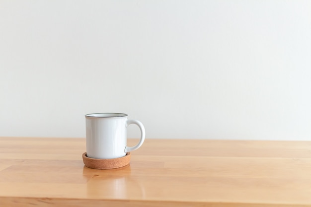 Tasse blanche de tasse de café chaud sur la table en bois avec le fond blanc
