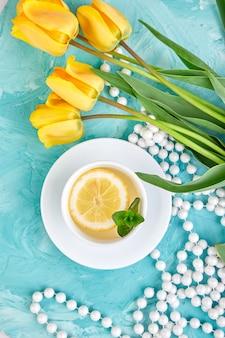 Tasse blanche de thé au citron plat poser.
