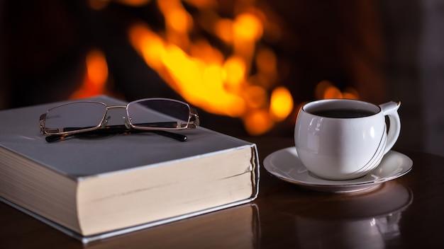 Tasse blanche de thé ou de café, verres et vieux livre près d'une cheminée sur une table en bois.