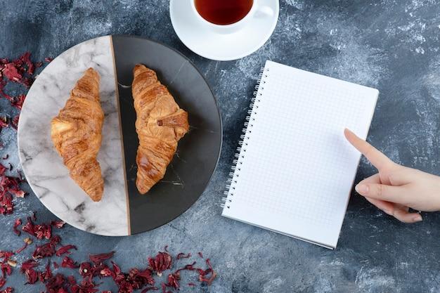 Une tasse blanche de thé chaud avec un cahier vide placé sur une table en marbre.