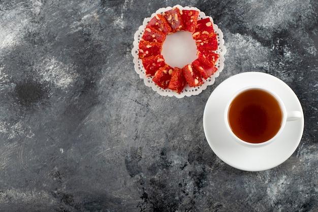 Une tasse blanche de thé chaud avec un dessert en tranches.