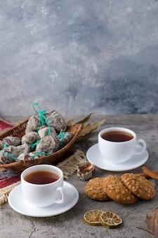 Une tasse blanche de thé chaud avec des fruits secs et des biscuits à l'avoine sur une table en pierre.