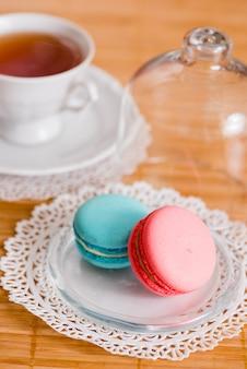 Tasse blanche de thé chaud, macaronis et biscuits sablés frais