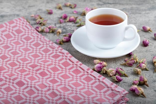 Tasse blanche de thé chaud avec des roses en herbe sur fond de pierre.