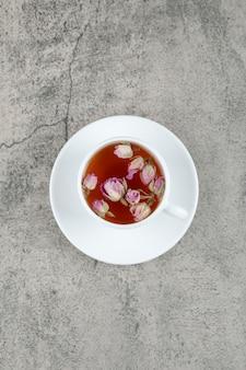 Une tasse blanche de thé chaud savoureux avec des fleurs roses fanées sur une table en pierre.