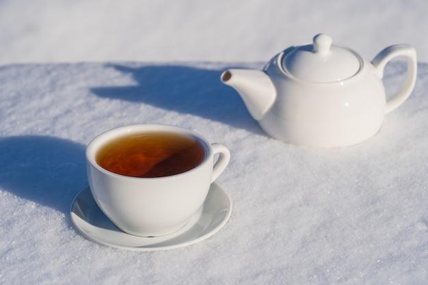 Tasse blanche de thé chaud et théière sur un lit de neige et fond blanc, gros plan. concept de matin d'hiver de noël