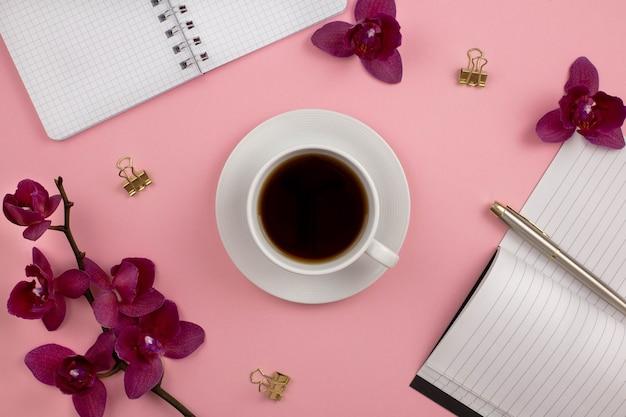 Tasse blanche de thé noir ou de café avec des fleurs d'orchidées sur fond rose.