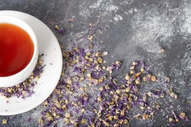 Tasse blanche de thé noir chaud avec des boutons de fleurs séchées placés sur une table gris foncé.