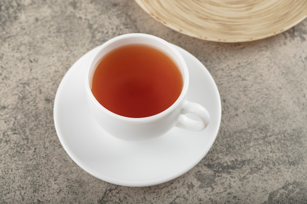 Tasse blanche de thé noir chaud sur la surface de la pierre.